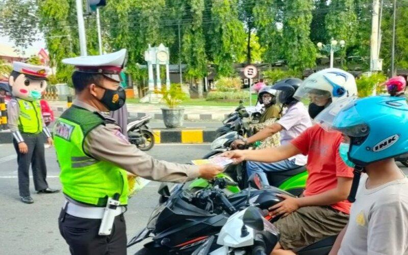 Petugas Satlantas Polres Situbondo bagikan brosur larangan mudik Lebaran 2021 kepada pengendara. Rabu (28/4/2021). - Antara/Novi H.