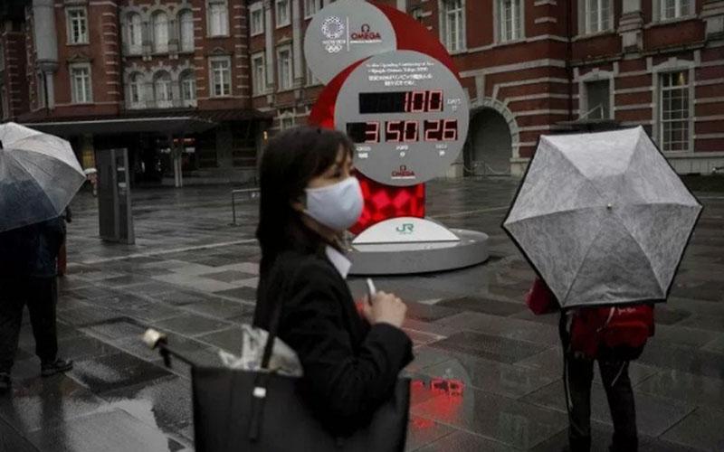 Seorang perempuan mengenakan masker berjalan di depan jam penghitung mundur 100 hari menjelang Olimpiade Tokyo 2020 di Tokyo, Jepang, Rabu (14/4/2021)./Antara - Reuters