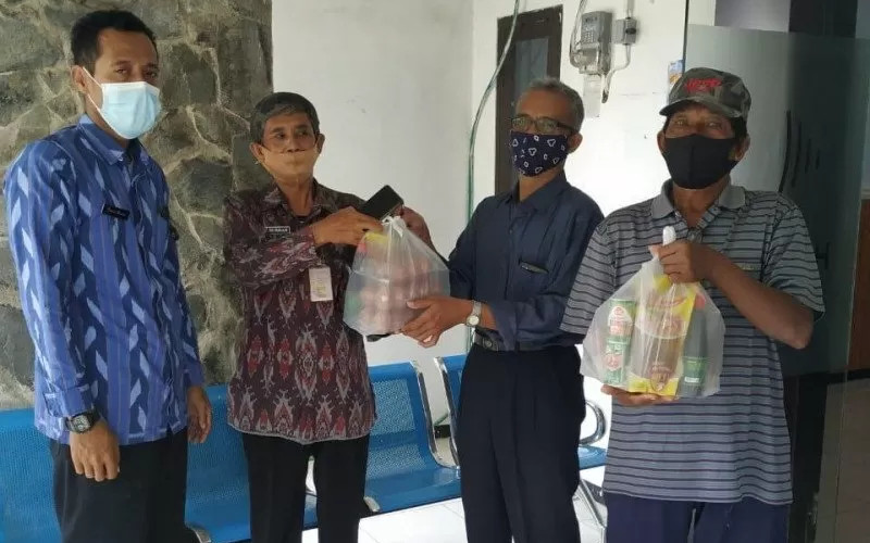 Petugas bersiap membagikan paket bahan pokok untuk warga isolasi mandiri karena Covid-19 di Kota Kediri, Jawa Timur.  - ANTARA.