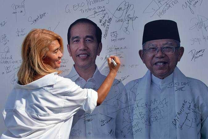 Seorang warga membubuhkan tanda tangan pada poster calon Presiden-Wakil Presiden Jokowi-Ma'ruf Amin dalam Deklarasi Dukungan Alumni SMA/SMK se-Bali di Denpasar, Bali, Jumat (29/3/2019). - ANTARA/Nyoman Hendra Wibowo