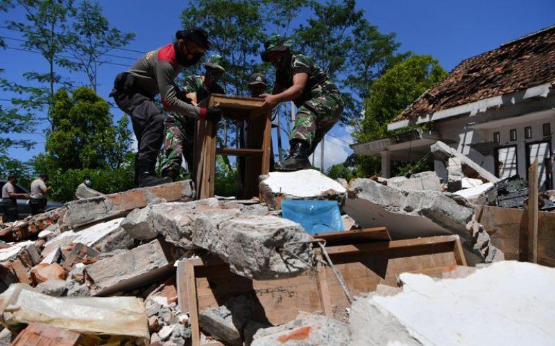 Polisi dan prajurit TNI AD membantu warga membersihkan puing-puing bangunan yang rusak akibat gempa di Desa Kaliuling, Lumajang, Jawa Timur, Senin (12/4/2021). Personel TNI dan Polri dikerahkan untuk membantu warga korban gempa untuk membersihkan sisa-sisa puing bangunan yang rusak akibat gempa - Antara Foto/Zabur Karuru