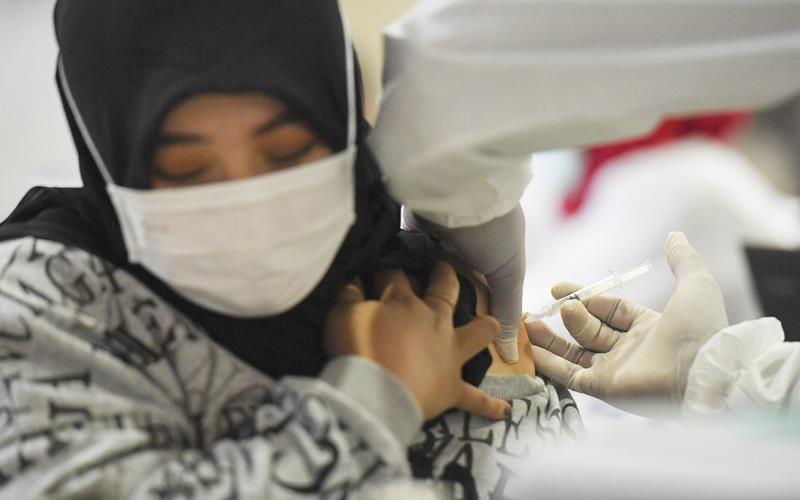 Petugas menyuntikan vaksin Covid-19 kepada pedagang di Pasar Tanah Abang Blok A, Jakarta, Rabu (17/2/2021). Vaksinasi Covid-19 tahap kedua yang diberikan untuk pekerja publik dan lansia itu dimulai dari pedagang Pasar Tanah Abang.  - Antara Foto/Hafidz Mubarak A