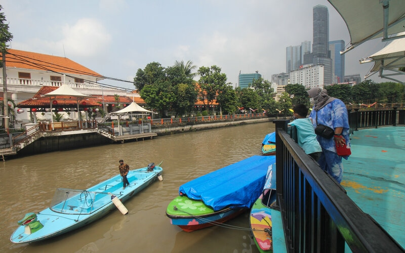 Warga mengamati perahu wisata yang melintas di Sungai Kalimas di Taman Prestasi Jalan Ketabang Kali, Surabaya, Jawa Timur, Sabtu (10/4/2021). - Antara/Didik Suhartono.