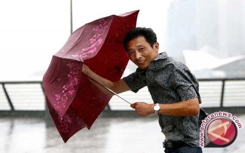 Ilustrasi: Seorang warga memegang payungnya dengan erat saat topan menyapu daerah pesisir Shanghai, China./ANTARA - REUTERS/Carlos Barria