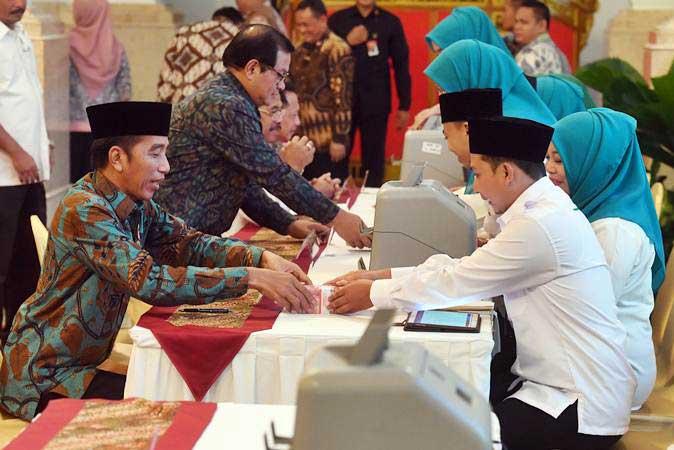 Ilustrasi - Presiden Joko Widodo (kiri) menyerahkan pembayaran zakat mal kepada petugas di Istana Negara, Jakarta, Kamis (16/5/2019). Presiden membayar zakatnya sebesar Rp55 juta. - ANTARA/Akbar Nugroho Gumay