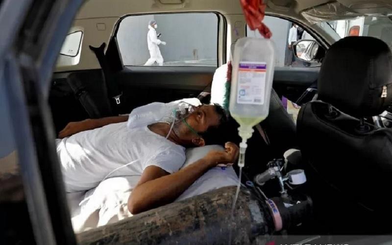 Seorang pasien dengan gangguan pernapasan berbaring di dalam mobil sambil menunggu untuk masuk rumah sakit Covid-19 untuk perawatan, di tengah penyebaran Covid-19 di Ahmedabad, India, Kamis (22/4/2021). - Antara/Reuters\r\n\r\n