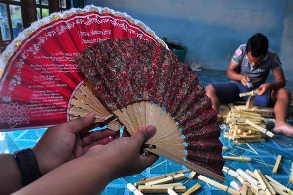 Seorang pekerja menyelesaikan proses pembuat kipas tangan di Kuwel, Keprabon, Klaten, Jawa Tengah - Antara