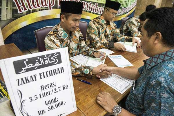 Umat muslim membayarkan zakat fitrah kepada panitia amil zakat di Masjid Istiqlal, Jakarta, Jumat (9/6). - Antara/M Agung Rajasa