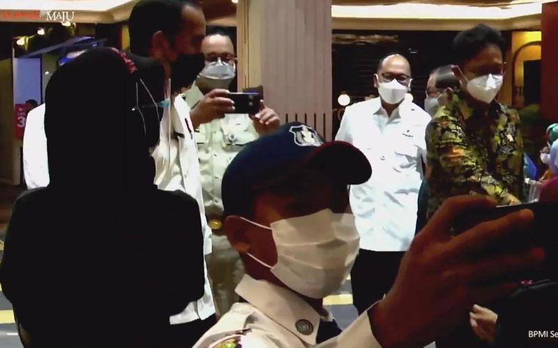 Gubernur DKI Jakarta Anies Baswedan menjadi fotografer dadakan Presiden Jokowi bersama warga di acara vaksinasi Covid/19 untuk pelaku usaha perdagangan di mal Grand Indonesia, Jakarta pada Senin, 3 Mei 2021 / Youtube Sekretariat Presiden
