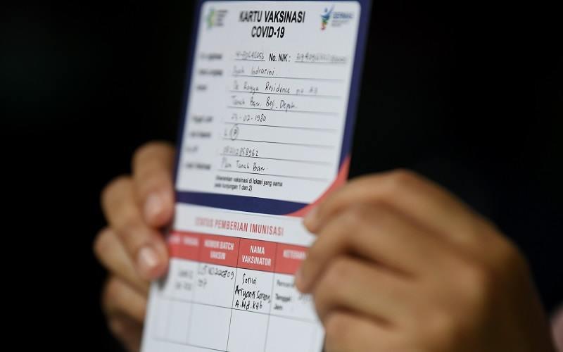 Tenaga kesehatan menunjukkan kartu vaksinasi COVID-19 seusai penyuntikan vaksin CoronaVac, di Puskesmas Tanah Baru, Depok, Jawa Barat, Jumat (15/1/2021). Sebanyak 1,48 juta tenaga kesehatan sebagai garda terdepan dalam melayani pasien COVID-19 akan divaksin secara bertahap hingga februari 2021. - Antara