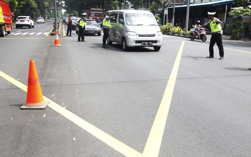Petugas gabungan memberhentikan dan memeriksa kendaraan asal luar Kota Solo yang melintas di Pos Simpang Faroka saat simulasi penyekatan larangan mudik di Solo, Jawa Tengah, Rabu (28/4/2021). - Antara/Maulana Surya.