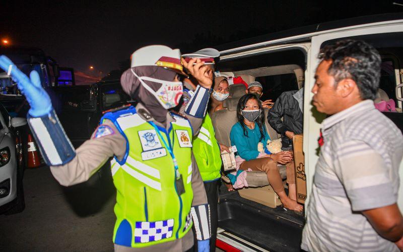 Petugas kepolisian mengarahkan calon pemudik yang terjaring razia penyekatan. - Antara Foto/Nova Wahyudi