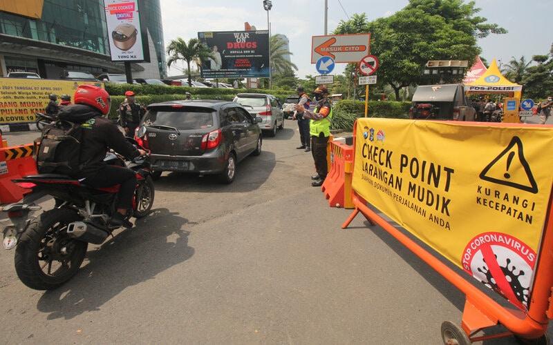 Polisi mengarahkan pengendara motor untuk melewati jalur yang benar saat simulasi penyekatan larangan mudik di Bundaran Waru, Surabaya, Jawa Timur, Kamis (29/4/2021). - Antara/Didik Suhartono.