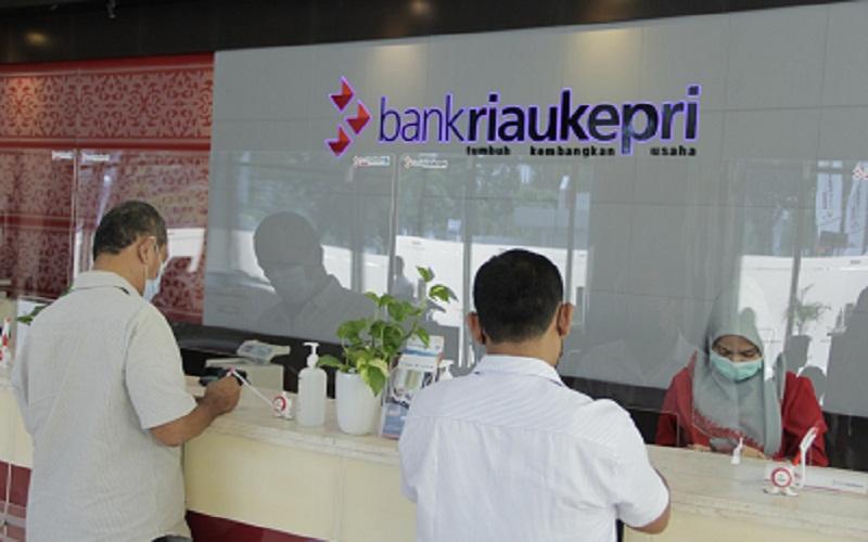 Pegawai Bank Riau Kepri tengah melayani nasabah, dengan penerapan protokol kesehatan yang ketat.  - Bisnis/Arif Gunawan