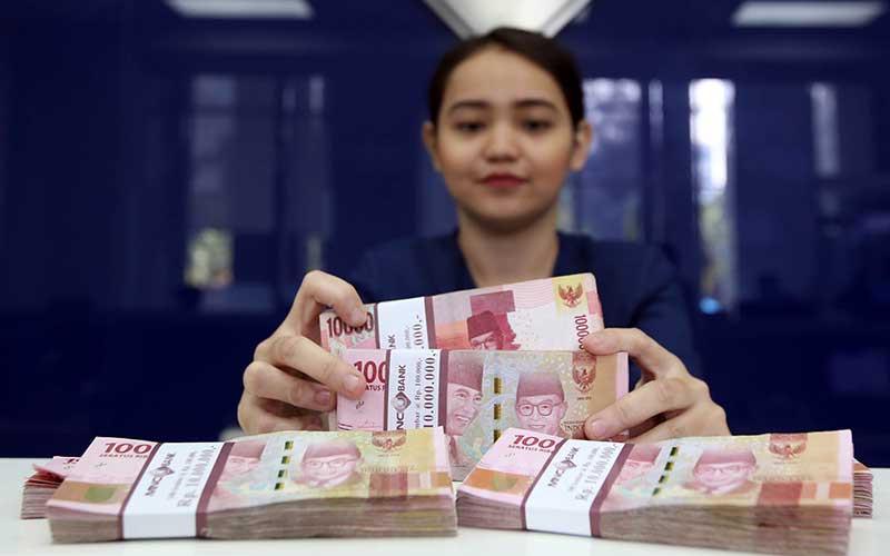 Ilustrasi - Karyawan menghitung uang pecahan Rp.100.000 di salah satu bank. - Bisnis/Abdullah Azzam
