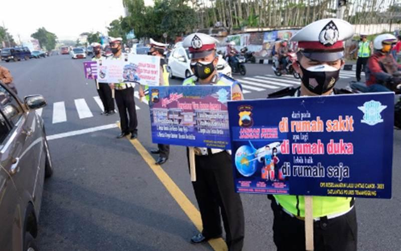 Polisi membawa poster saat kampanye larangan mudik Lebaran di kawasan Terminal Madureso, Temanggung, Jateng, Rabu (21/4/2021). - Antara/Anis Efizudin