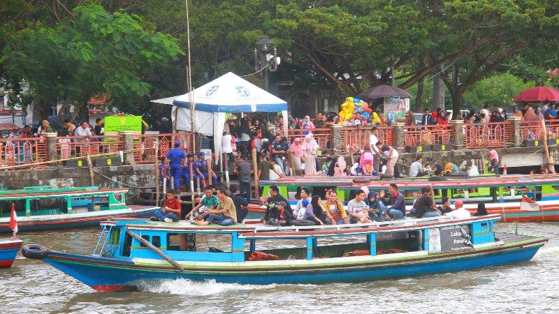 Sejumlah warga menaiki perahu bermesin (kelotok) untuk menyusuri Sungai Martapura, Banjarmasin, Kalimantan Selatan, Kamis (6/6/2019).Wisata susur Sungai Martapura menjadi pilihan warga untuk mengisi libur Hari Raya Idulfitri di Banjarmasin. - ANTARA FOTO/Bayu Pratama S
