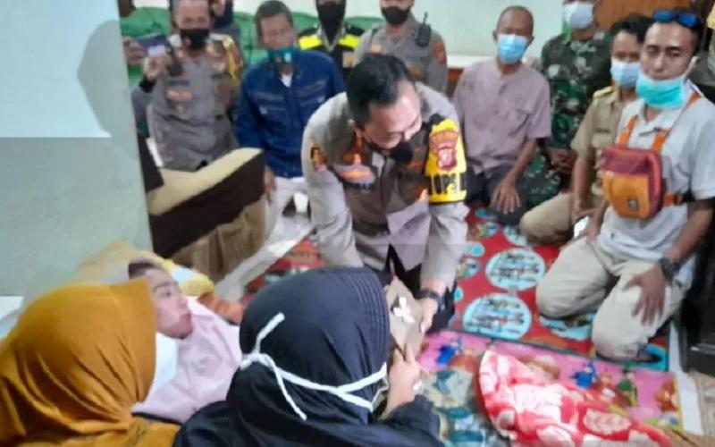 Kapolres Sukabumi AKBP Lukman saat memberikan bantuan dari Presiden RI Jokowi untuk Susan Antela guru SMAN 1 Cisolok, Kabupaten Sukabumi yang mengelami Guillain Barre Syndrome GBS. - Antara\r\n