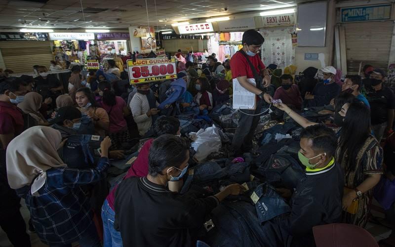 Sejumlah warga berbelanja pakaian di Blok B Pusat Grosir Pasar Tanah Abang, Jakarta Pusat, Minggu (2/5/2021). Gubernur DKI Anies Baswedan mengakui adanya lonjakan pengunjung di pusat tekstil terbesar se-Asia Tenggara tersebut, dari sekitar 35.000 pengunjung pada hari biasa menjadi sekitar 87.000 orang pada akhir pekan ini sehingga pihaknya menyiagakan sekitar 750 petugas untuk menjaga kedisiplinan protokol kesehatan untuk mencegah penularan Covid-19. ANTARA FOTO/Aditya Pradana Putra - foc.\r\n