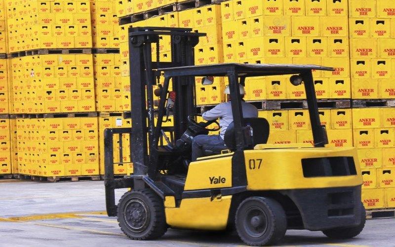 Petugas mengoperasikan forklift untuk memindahkan kerat-kerat berisi botol bir./ - deltajkt.co.id
