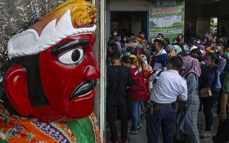 Sejumlah warga bergantian memasuki pintu Blok B di Pusat Grosir Pasar Tanah Abang, Jakarta Pusat, Minggu (2/5/2021). Gubernur DKI Anies Baswedan mengakui adanya lonjakan pengunjung di pusat tekstil terbesar se-Asia Tenggara tersebut dari sekitar 35.000 pengunjung pada hari biasa menjadi sekitar 87.000 orang pada akhir pekan ini sehingga pihaknya menyiagakan sekitar 750 petugas untuk menjaga kedisiplinan protokol kesehatan untuk mencegah penularan Covid-19 - Antara
