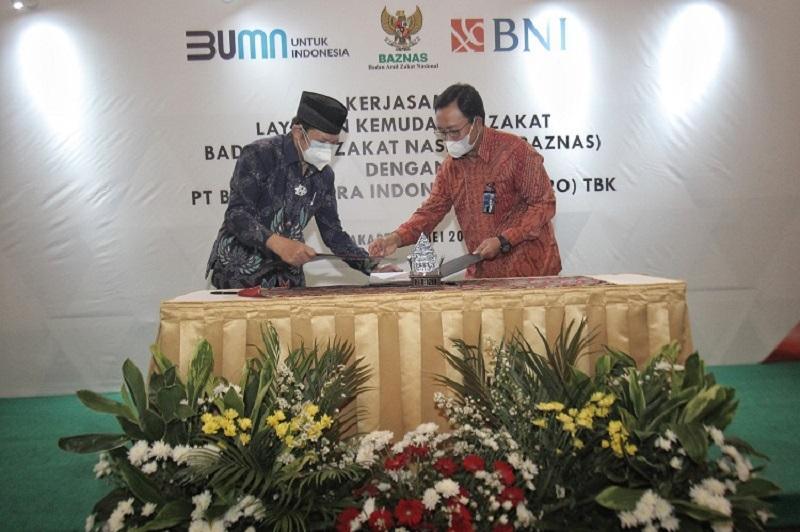 Ketua Baznas Noor Ahmad (kiri) dan Direktur Hubungan Kelembagaan BNI Sis Apik Wijayanto (kanan) menandatangani Nota Kesepahaman tentang penciptaan kanal digitalisasi pengelolaan zakat di Jakarta, Rabu (5 - 5). / Dok. BNI