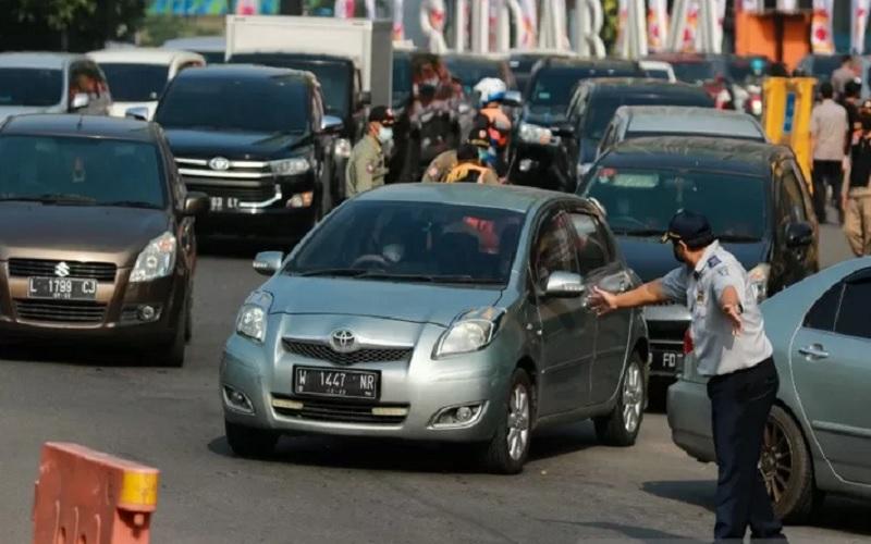 Petugas mengatur lalu lintas kendaraan yang akan masuk ke Kota Surabaya saat hari pertama larangan mudik di kota setempat, Kamis (6/5/2021). - Antara \r\n