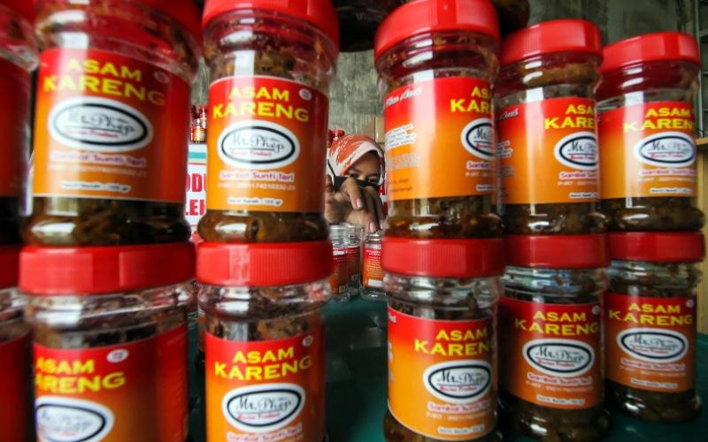 Pekerja memberi label pada botol kemasan Asam Udang di Rumah produksi Mr. Phep Lhokseumawe, Aceh, Senin ( 29/3/2021). Bisnis UMKM kuliner siap saji yang terdampak pandemi COVID-19 tersebut bertahan dengan melakukan inovasi pelayanan berbasis online dengan menambah aneka varian seperti sambal sunti, keumamah (ikan kayu), Asam Kareng (sambal Teri) yang dijual dari harga Rp15 ribu hingga Rp20 ribu per botol agar tidak gulung tikar. - ANTARA FOTO/Rahmad