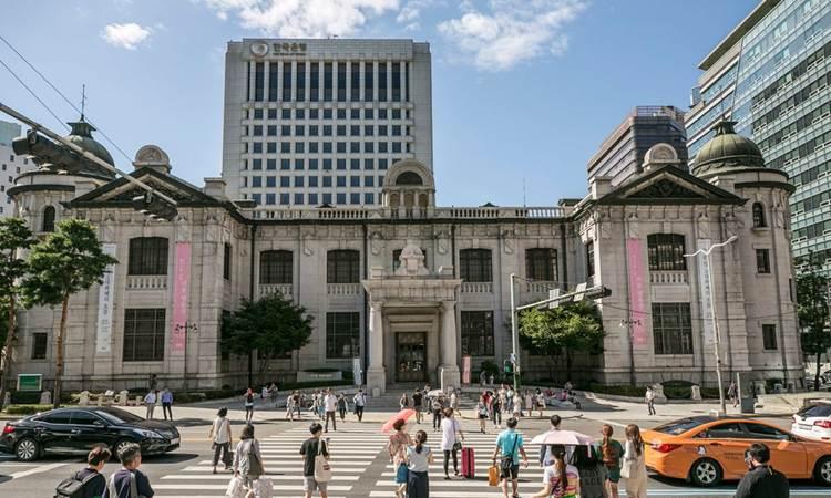 Pejalan kaki menyeberang di jalan menuju pintu masuk ke museum Bank of Korea (BOK) yang terdapat di tengah kompleks kantor pusat Bank of Korea di Seoul, Korea Selatan. - Bloomberg/Jean Chung