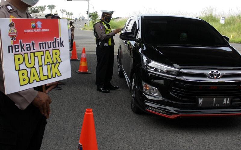 Petugas memeriksa kelengkapan surat dan KTP saat hari pertama penyekatan larangan mudik di Perbatasan Surabaya-Sidoarjo di Tambak Sumur, Sidoarjo, Jawa Timur, Kamis (6/5/2021). Penyekatan di sejumlah lokasi perbatasan tersebut serentak saat penerapan larangan mudik Lebaran 2021 sebagai upaya pencegahan penularan Covid-19. - Antara/Umarul Faruq.