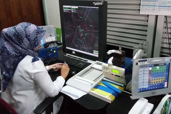 Caption: Seorang pegawai AirNav sedang mengamati pergerakan pesawat di Air Traffic Controller Working Positions Bandara Supandio Pontianak - Bisnis.com/Rio Sandy Pradana.