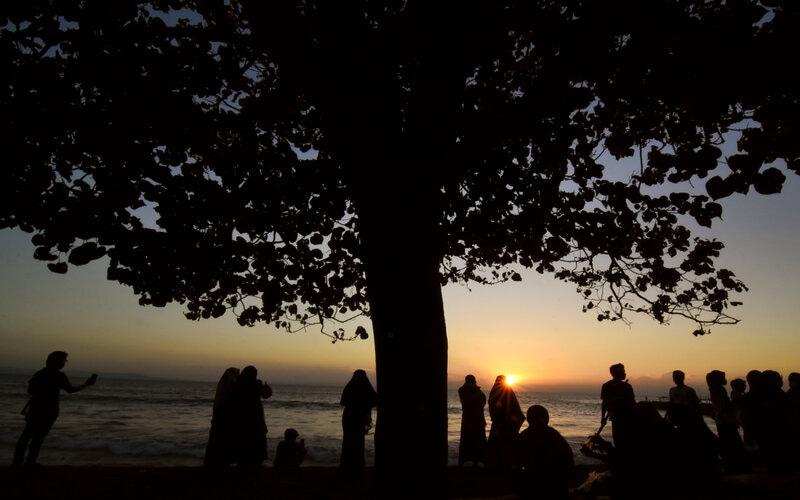 Sejumlah pengunjung menikmati matahari terbenam di pantai Loang Baloq, Mataram, NTB, Senin (12/4/2021). Pantai Loang Baloq yang berada di pinggiran kota Mataram tersebut setiap sore ramai dikunjungi warga kota untuk rekreasi bersama keluarga sambil menikmati matahari terbenam. - Antara/Ahmad Subaidi.