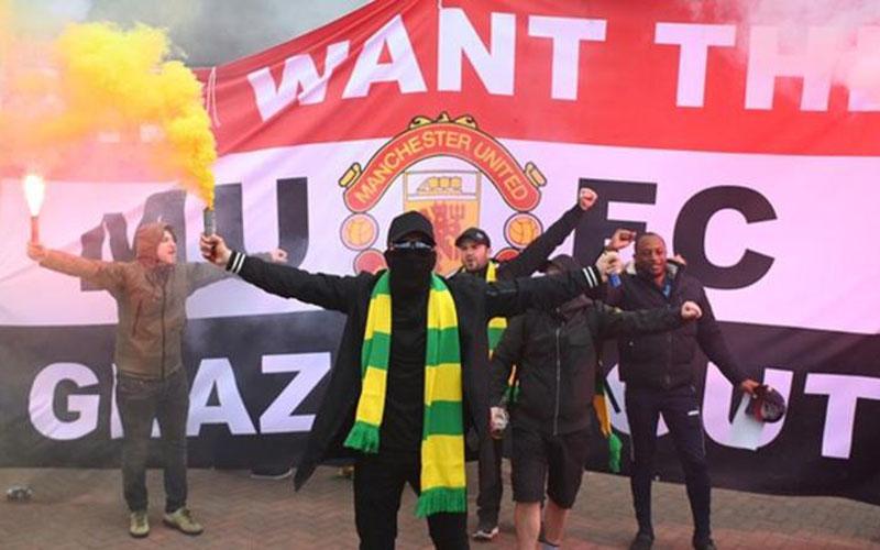 Fans Manchester United melakukan demo ingin keluarga Glazer pergi. - BBC