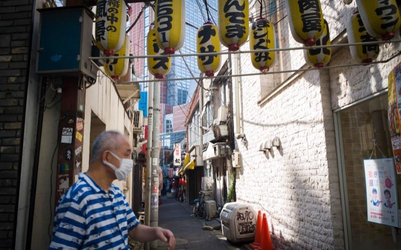Seorang warga mengenakan masker untuk mencegah penularan virus Covid-19, berdiri di Kota Tokyo, Jepang. - Bloomberg