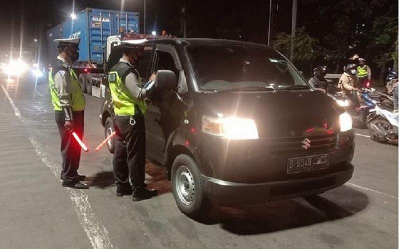 Polri melakukan pemeriksaan kendaraan minibus yang diduga travel gelap dan hendak membawa pemudik di TL Perintis Kemerdekaan, Jakarta Utara, Kamis (6/5/2021) malam. JIBI - Bisnis/Nancy Junita @tmcpoldametro