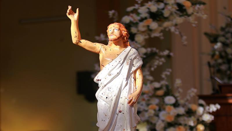 Patung Yesus Kristus tampak terciprat darah ketika sinar Matahari masuk melalui atap yang hancur di dalam Gereja St Sebastian di Negombo, Sri Lanka 21 April 2019. -  Reuters