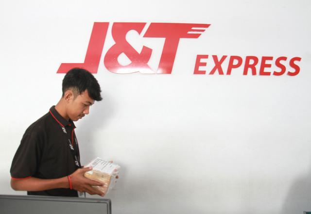 Karyawan pengiriman barang J&T memindahkan barang kiriman di Makassar, Sulawesi Selatan. - Bisnis/Paulus  Tandi Bone