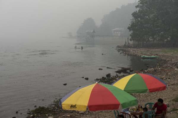 Wisatawan duduk di tepi Danau Singkarak yang diselimuti asap di Solok, Sumatra Barat. - Antara/M. Agung Rajasa