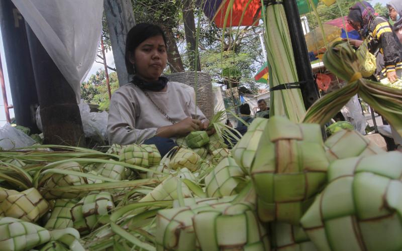 Pedagang membuat kulit ketupat di salah satu pasar di Jakarta, Selasa (11/5/2021). Menjelang hari Idulfitri, marak pedagang kulit ketupat musiman menggelar dagangannya di pasar-pasar hingga ke tepi jalan. Harganya Rp10.000-Rp15.000 per 10 unit.  - Bisnis/Himawan L Nugraha