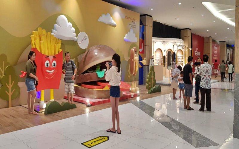 Pengunjung Pakuwon City Mall Surabaya tengah berfoto dengan salah satu ikon kuliner saat Hari Raya Idulfitri, Kamis (13/5/2021) - Bisnis/Peni Widarti