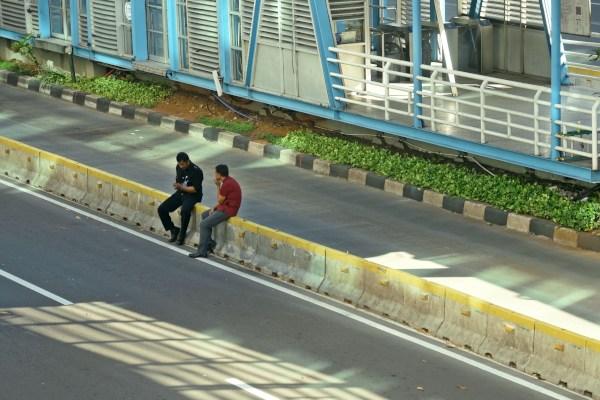 Dua warga duduk di atas beton pemisah jalur TransJakarta di Jalan MH Thamrin, Jakarta Pusat - ANTARA FOTO/Aditya Pradana Putra