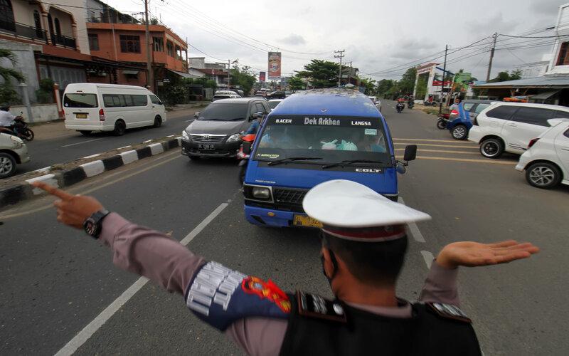 Petugas gabungan Operasi Ketupat Seulawah Polres Lhokseumawe mengarahkan mobil angkutan umum untuk putar balik di pos penyekatan mudik jalan lintas Aceh-Sumut, Lhokseumawe, Aceh, Kamis (6/5/2021). Penyekatan itu untuk mencegah keluar dan masuknya pemudik ke Aceh pada masa larangan mudik Lebaran 2021. - Antara/Rahmad.