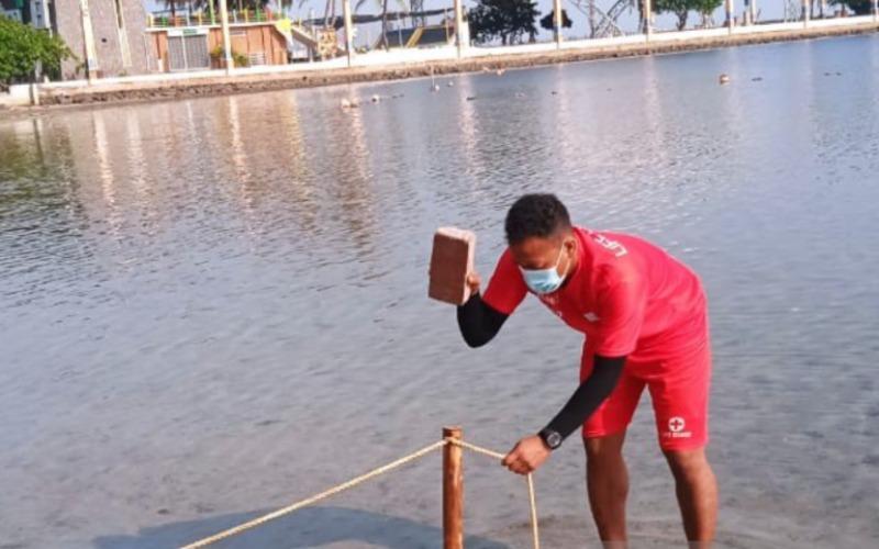 Petugas memasang tali pancang untuk membatasi area pantai dengan laut di kawasan Taman Impian Jaya Ancol, Jakarta Utara, Sabtu (15/5/2021)./Antara - HO/Taman Impian Jaya Ancol
