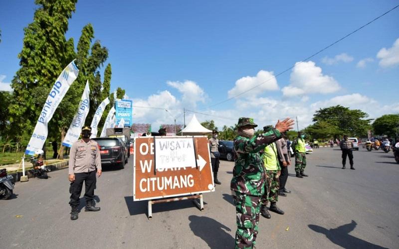 Aparat gabungan berjaga di pintu masuk kawasan wisata di Pangandaran - Bisnis/Wisnu Wage
