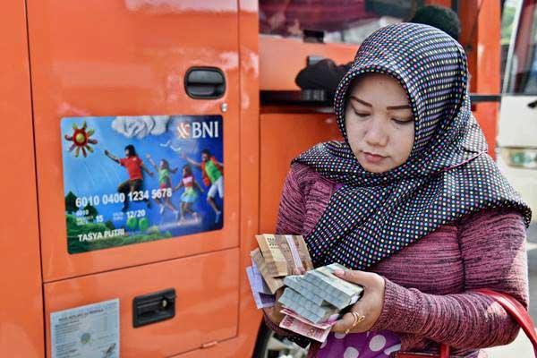 Warga membawa uang yang baru ditukarkan di loket mobil kas keliling, di Semarang, Jawa Tengah, Selasa (6/6). - Antara/R. Rekotomo