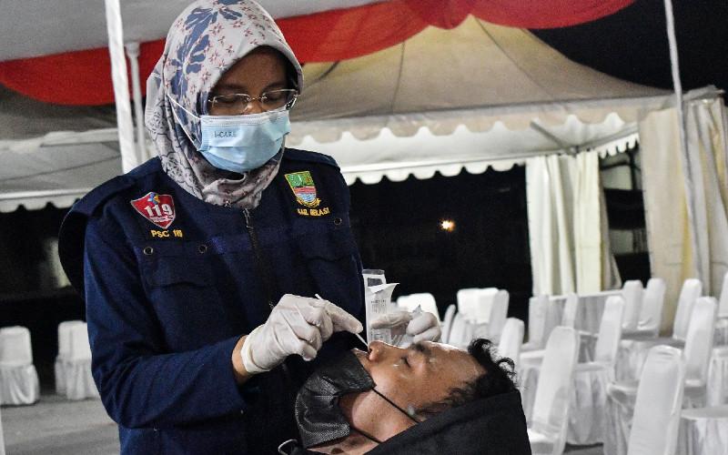 Petugas kesehatan melakukan tes rapid antigen ke pemudik di posko penyekatan arus balik mudik di Cikarang, Kabupaten Bekasi, Jawa Barat, Sabtu (15/5/2021). Pemerintah Kabupaten Bekasi menyediakan 2.000 alat tes rapid antigen dan 450 ruang isolasi untuk pemudik yang positif Covid-19.  - ANTARA