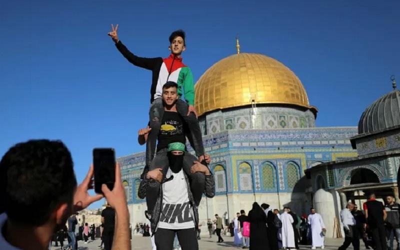 Seorang pemuda Palestina memotret rekannya yang berpose dengan latar belakang Dome of the Rock setelah shalat Idulfitri 1442 H pada akhir bulan suci Ramadan di kompleks Masjid Al-Aqsa, yang dikenal umat muslim sebagai Tempat Suci dan Yahudi sebagai Temple Mount, di Kota Tua Yerusalem di tengah pertempuran Israel-Gaza, Kamis (13/5/2021). - Antara\r\n