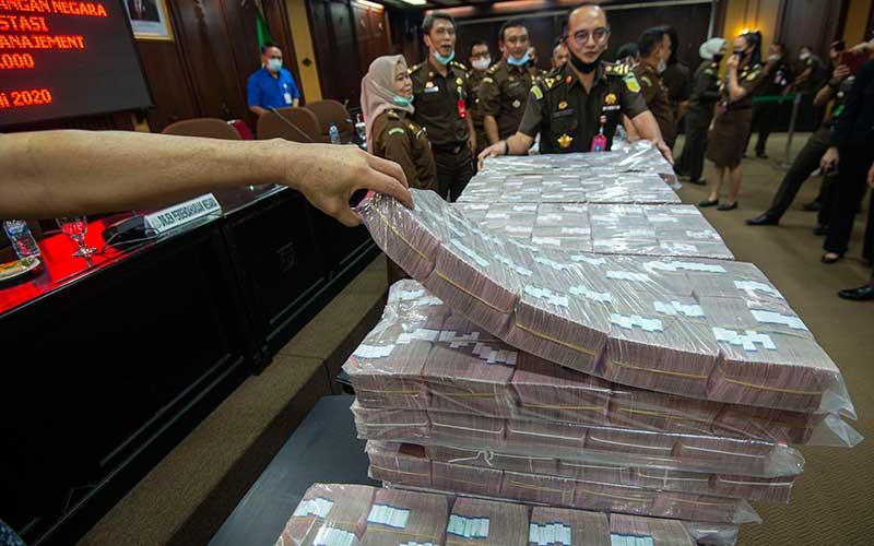 Petugas menata barang bukti berupa uang sitaan di kantor Kejaksaan Agung (Kejagung), Jakarta, Selasa (7/7/2020). Kejagung menunjukan uang sebesar Rp77 miliar dalam perkara dugaan tindak pidana korupsi pengelolaan keuangan dan dana investasi pada PT Asuransi Jiwasraya (Persero) tahun 2008-2018. ANTARA FOTO - Aditya Pradana Putra