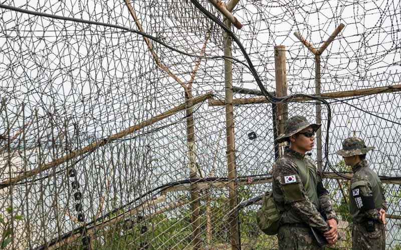Seorang polisi milter Korea Selatan sedang menjaga Zona Demiliterisasi di Goseong, Korea Selatan. - Bloomberg/Jean Chung