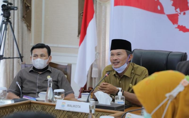 Walikota Palembang Harnojoyo (tengah) menyimak arahan Presiden RI Joko Widodo secara virtual di ruang kerjanya. istimewa